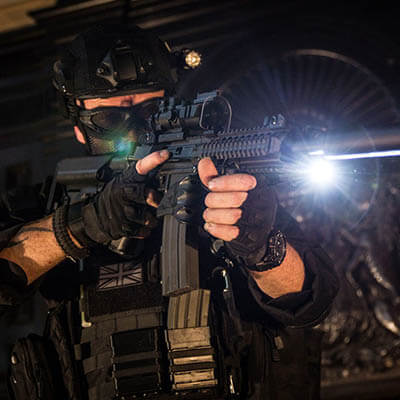 Bristol Airsoft Shop - man with military grade replica airsoft rifle and torch